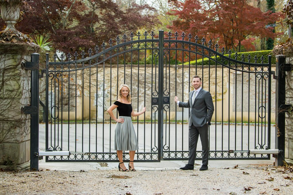 Engaged couple at Oheka Castle's driveway gate