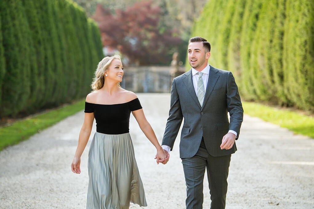 Engaged couple walking at Oheka's driveway