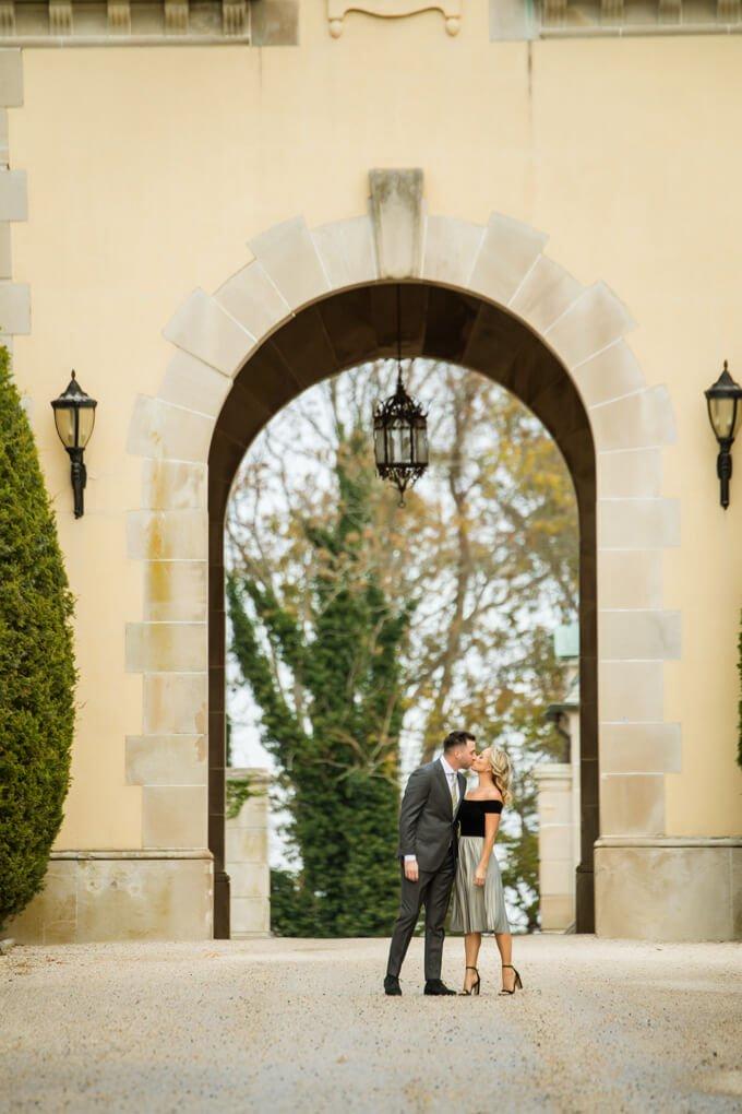 Engaged couple kissing at Oheka's driveway
