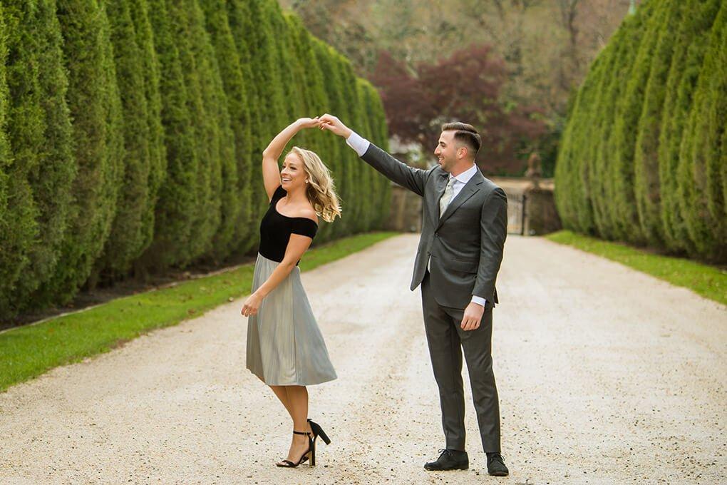 Engaged couple having fun at Oheka's driveway