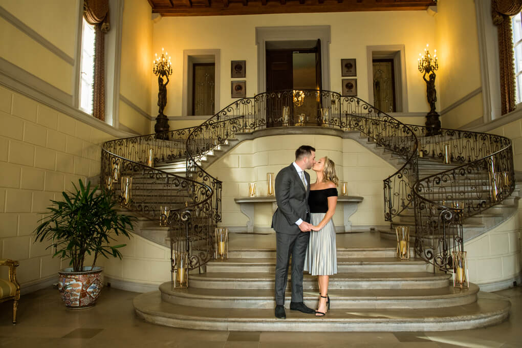 Couple kissing in front of Oheka Castle stairs