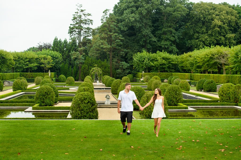 Couple walking at Oheka Castle with gardens in the background