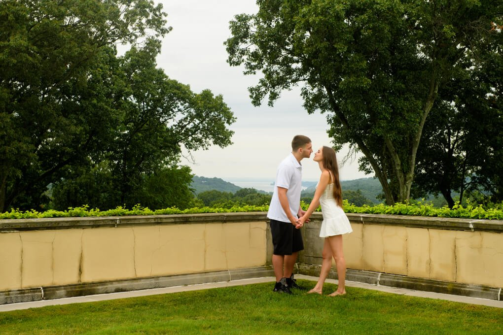A couple about to kiss with the harbor in the background Oheka Castle