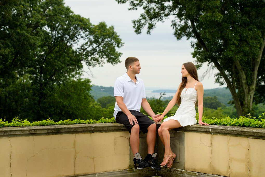 A couple sitting with the harbor in the background Oheka Castle