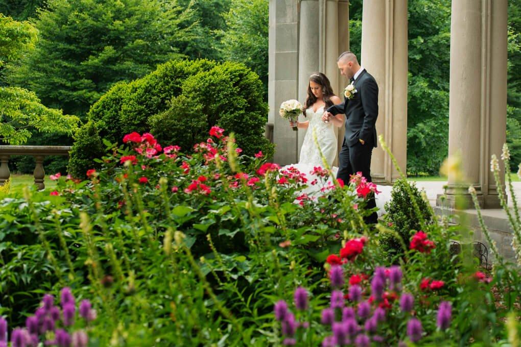Bride and groom walking at planting Fields Arboretum
