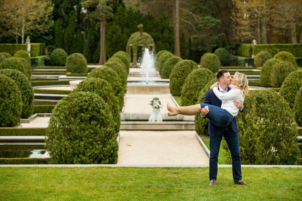 Engaged couple kissing with Oheka Castle garden background