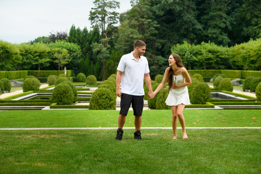 A couple laughing in the garden at Oheka Castle