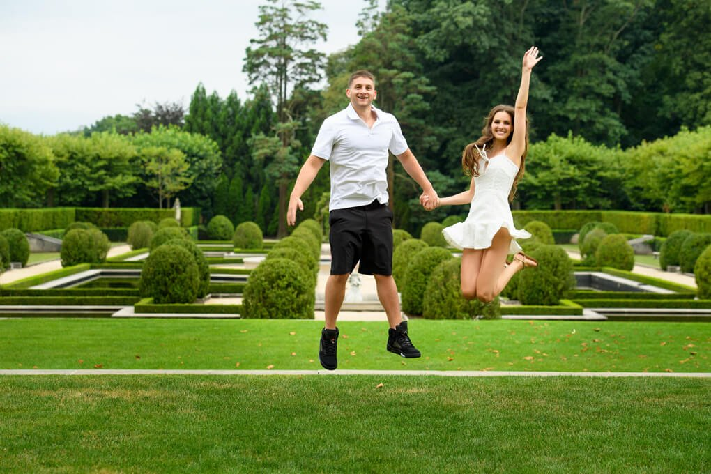 Couple jumping in the air at Oheka Castle