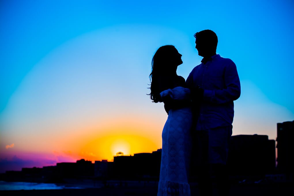 Engaged couple silhouette in long beach